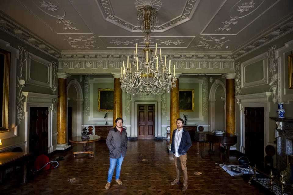 Neil Watt (left) with his partner Kris Reid standing under the chandelier in Castle Ward's reception hall which they cleaned during the pandemic (Liam McBurney/PA)