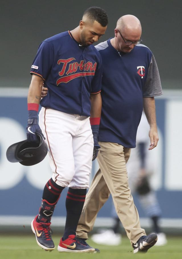 Minnesota Twins' Eddie Rosario, left, is helped off the field by trainer Tony Leo after he twisted his ankle while rounding first base on a hit during the third inning of the team's baseball game against the Tampa Bay Rays on Wednesday, June 26, 2019, in Minneapolis. (AP Photo/Jim Mone)