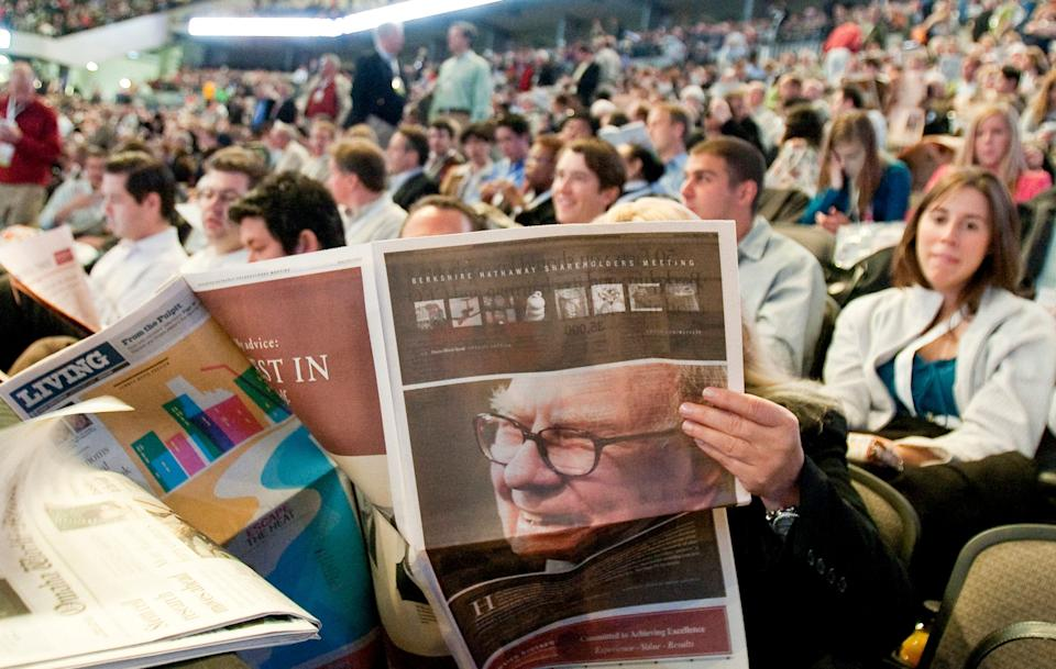 The picture of Berkshire Hathaway Chairman and CEO Warren Buffett is seen in a newspaper in Omaha, Neb., Saturday, May 1, 2010, as shareholders pack the Qwest Center arena well ahead of the shareholders meeting start time.(AP Photo/Nati Harnik)