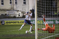 Tottenham's Carlos Vinicius scores his side's first goal passing Marine's goalkeeper Bayleigh Passant, right, during the English FA Cup third round soccer match between Marine and Tottenham Hotspur at Rossett Park stadium in Crosby, Liverpool, Sunday, Jan. 10, 2021. (Clive Brunskill/Pool via AP)
