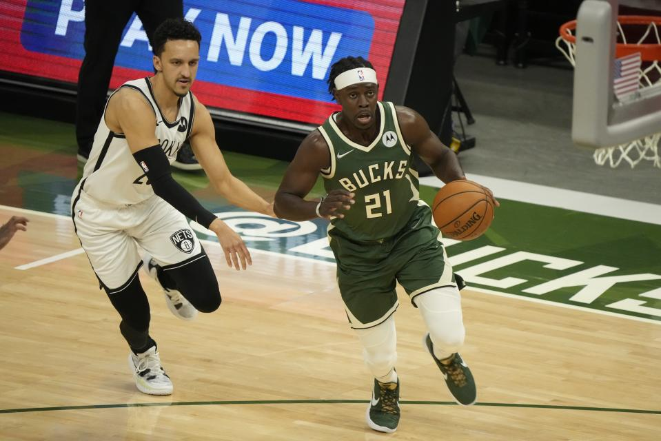 Milwaukee Bucks' Jrue Holiday drives past Brooklyn Nets' Landry Shamet during the first half of Game 3 of the NBA Eastern Conference basketball semifinals game Thursday, June 10, 2021, in Milwaukee. (AP Photo/Morry Gash)