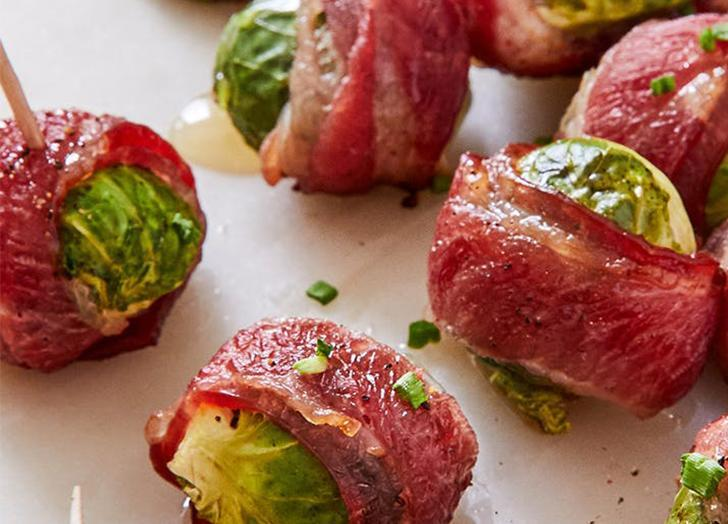 """<h2>16. Crispy Bacon-Wrapped Brussels Sprouts</h2> <p>These will definitely stand out in a sea of sad party appetizers. Make a double batch—they'll go fast.</p> <p><a class=""""link rapid-noclick-resp"""" href=""""https://www.purewow.com/recipes/crispy-bacon-wrapped-brussels-sprouts"""" rel=""""nofollow noopener"""" target=""""_blank"""" data-ylk=""""slk:Get the recipe"""">Get the recipe</a></p>"""