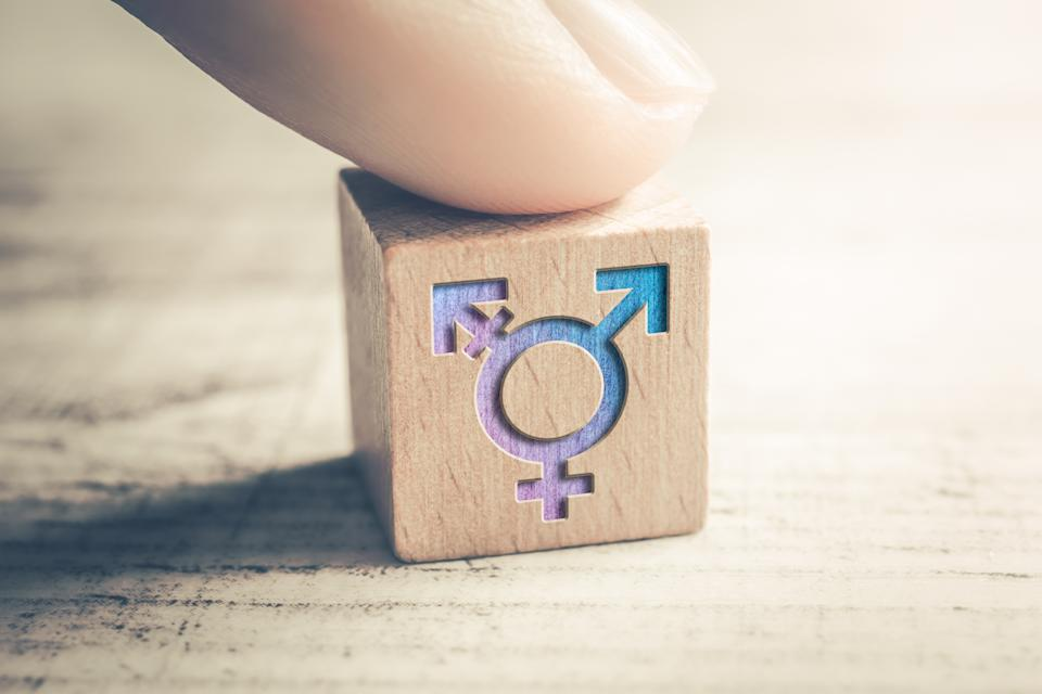Transgender, LGBT or Intersex Icon On Wodden Block On A Table Arranged By A Finger