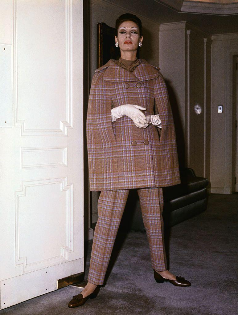 <p>Designer Norman Norell took traditional elements, including wool and plaid, and constructed a three-piece outfit. A cape and fuller pants, as opposed to peacoat and skirt, gave this look a modernized twist.<br></p>