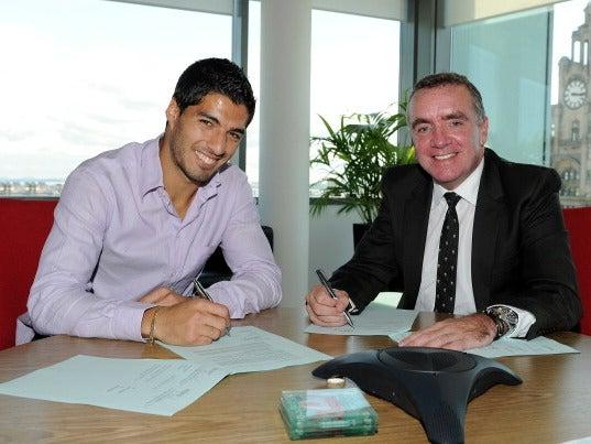 Luis Suarez signs a new Liverpool contract with Managing Director Ian Ayre in 2012: Getty