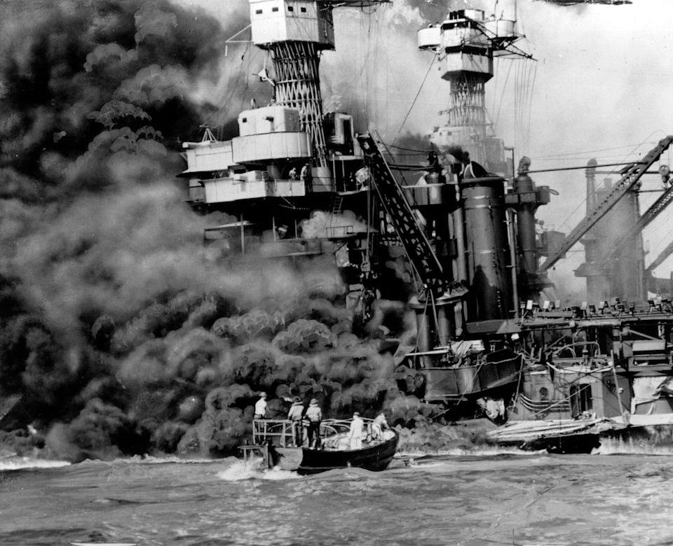 a small boat rescues a crew member from the water as heavy smoke rolls out of the stricken USS West Virginia after the Japanese bombing of Pearl Harbor, Hawaii. Two men can be seen on the superstructure, upper center. The mast of the USS Tennessee is beyond the burning West Virginia. Saturday marks the 72nd anniversary of the attack that brought the United States into World War II.