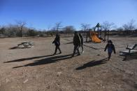 Angelica Rodriguez walks her U.S. citizen children; aged 13, 15 and 6, from a playground to their home on Wednesday, Dec. 23, 2020, in Santa Fe, N.M. Rodriguez and her husband, both cooks, struggled to pay rent this year as their hours were cut in half. As immigrants in the country without legal permission, they're ineligible for state unemployment or federal stimulus money. (AP Photo/Cedar Attanasio)