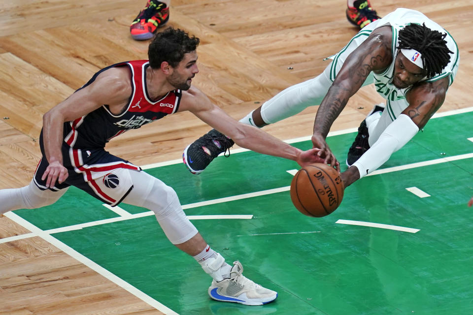 Washington Wizards guard Raul Neto, left, and Boston Celtics center Robert Williams III scramble for the ball during the first half of an NBA basketball Eastern Conference play-in game Tuesday, May 18, 2021, in Boston. (AP Photo/Charles Krupa)