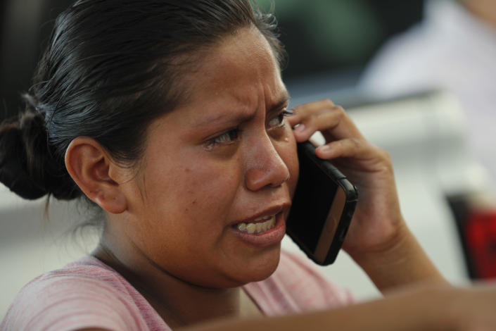 A migrant cries as she speaks on the phone, at an immigration center on the International Bridge 1, in Nuevo Laredo, Mexico, Tuesday, July 16, 2019. A U.S. policy to make asylum seekers wait in Mexico while their cases wind through clogged U.S. immigration courts has also expanded to the violent city of Nuevo Laredo. (AP Photo/Marco Ugarte)