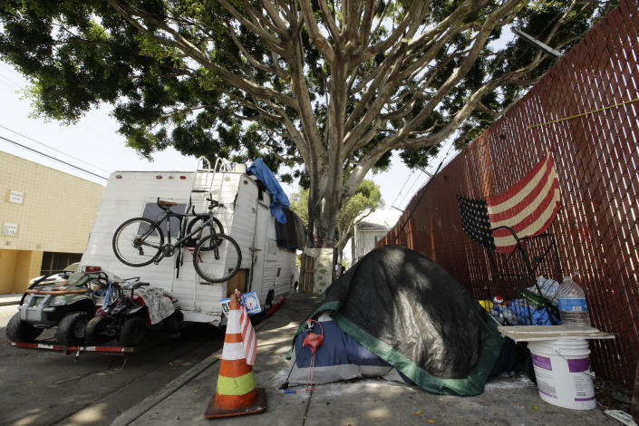 A RV vehicle is parked next to a tent on the streets in an industrial area of Los Angeles, Wednesday, July 31, 2019. (AP Photo/Damian Dovarganes)
