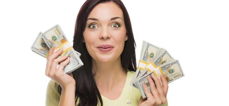 An excited looking woman holding up cash in each hand