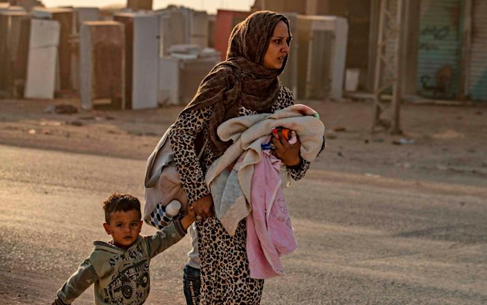 A woman flees with her children in Ras al-Ain as Turkey begins its attack - AFP
