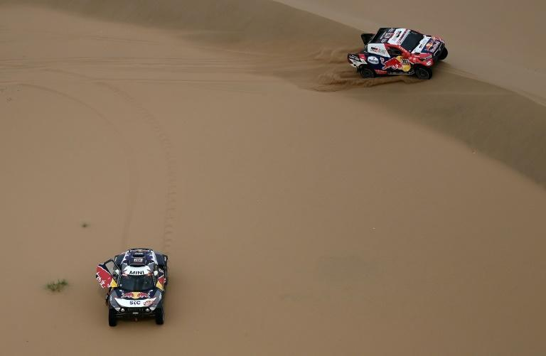 Sands of time: Nasser Al-Attiyah swept past Stephane Peterhansel as the Frenchman changed a tyre, but with one stage to go the Qatari still trails by a quarter of an hour
