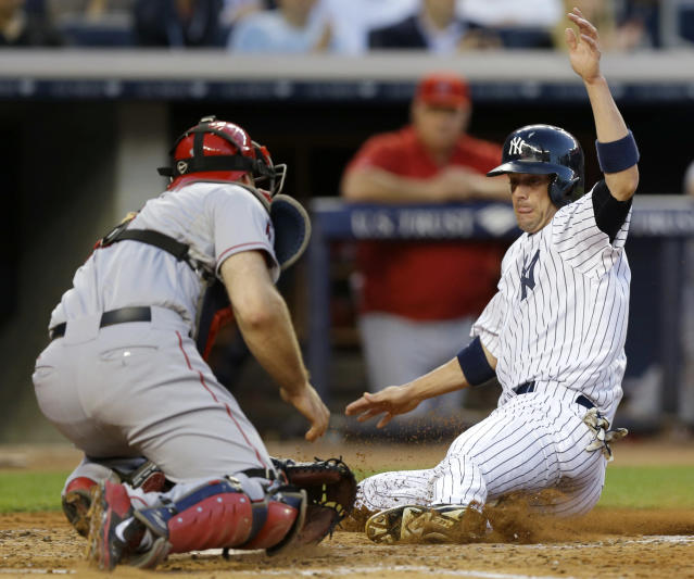 New York Yankees' Chris Stewart slides safely home against Los Angeles Angels catcher Chris Iannetta in the second inning of a baseball game Wednesday, Aug. 14, 2013, in New York. (AP Photo/Kathy Willens)