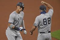 New York Yankees' Aaron Judge (99) is congratulated by Phil Nevin (88) after hitting a two run home run off Cleveland Indians starting pitcher Shane Bieber (57) in the first inning of Game 1 of an American League wild-card baseball series, Tuesday, Sept. 29, 2020, in Cleveland. (AP Photo/David Dermer)