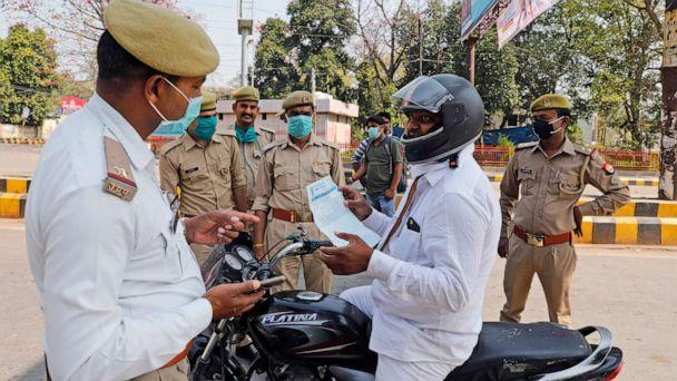 PHOTO: A commuter shows a doctor's prescription to policemen keeping guard during a complete lockdown amid growing concerns of coronavirus in Prayagraj, India, March 24, 2020. (Rajesh Kumar Singh/AP)