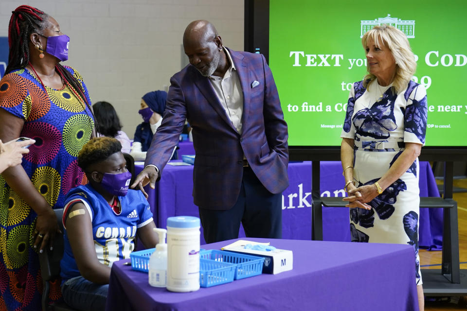 Former Dallas Cowboy and Football Hall of Famer Emmitt Smith talks with a COVID-19 vaccine recipient during a tour of vaccination site at Emmett J. Conrad High School in Dallas, Tuesday, June 29, 2021. First lady Jill Biden looks on at right. (AP Photo/Carolyn Kaster, Pool)