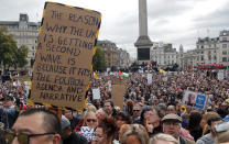 FILE - In this Saturday, Sept. 26, 2020 file photo people take part in a 'We Do Not Consent' rally at Trafalgar Square, organised by Stop New Normal, to protest against coronavirus restrictions, in London. (AP Photo/Frank Augstein)