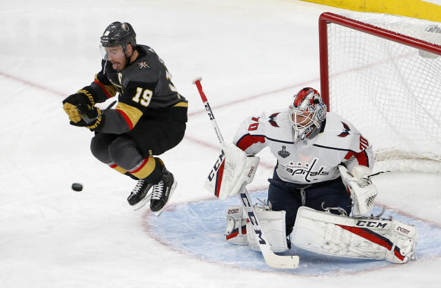 Vegas Golden Knights right wing Reilly Smith, left, jumps out of the way of a shot that was stopped by Washington Capitals goaltender Braden Holtby during the third period in Game 2 of the NHL hockey Stanley Cup Finals on Wednesday, May 30, 2018, in Las Vegas. (AP Photo/Ross D. Franklin)