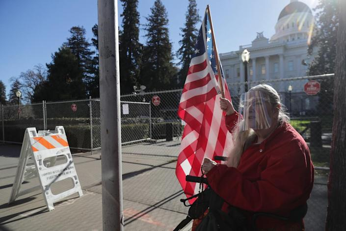 France Driscoll holding an American flag and rosary in front of state Capitol in Sacramento Saturday.