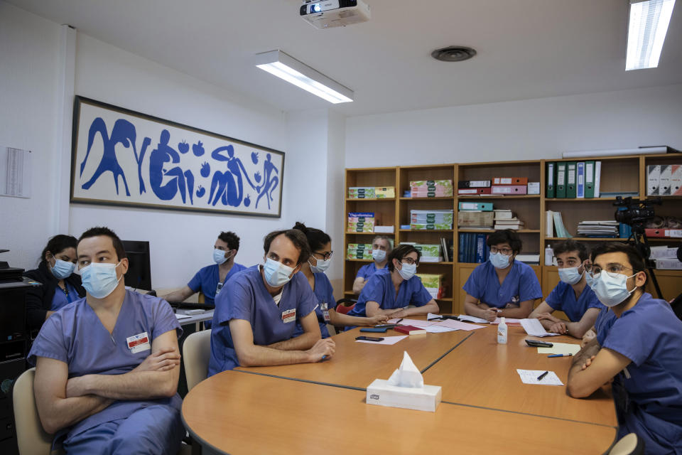 Medical staff, including Dr. Alexy Tran Dinh, left, attend an afternoon meeting at Bichat Hospital, AP-HP, in Paris, Thursday, April 22, 2021. France still had nearly 6,000 critically ill patients in ICUs this week as the government embarked on the perilous process of gingerly easing the country out of its latest lockdown, too prematurely for those on pandemic frontlines in hospitals. President Emmanuel Macron's decision to reopen elementary schools on Monday and allow people to move about more freely again in May, even though ICU numbers have remained stubbornly higher than at any point since the pandemic's catastrophic first wave, marks another shift in multiple European capitals away from prioritizing hospitals. (AP Photo/Lewis Joly)