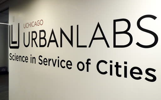 In this Wednesday, April 25, 2018 photo, a sign displays the name of University of Chicago-Crime Lab in Chicago. An unusual partnership involving the five major pro sports teams in Chicago is helping fight youth violence in the city. The Chicago Sports Alliance was unveiled in December. The teams announced a total of $1 million in one-time grants to programs and groups addressing violence, including the crime lab. (AP Photo/Nam Y. Huh)