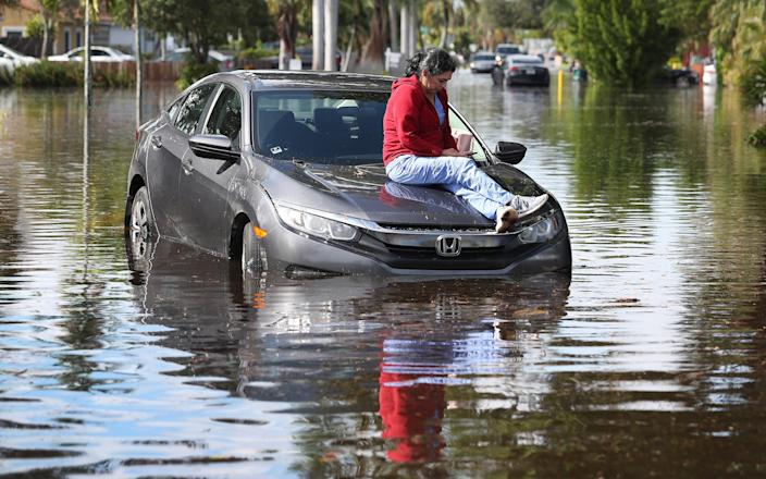 Stephanie Soto sits on the hood of her car after it stalled in floodwaters as she was driving Dec. 23, 2019, in Hollywood, Fla.