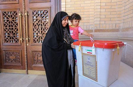 An Iranian woman holds a girl as she casts her vote during a second round of parliamentary elections, in Shiraz, Iran April 29, 2016. Farsnews.com/Handout via REUTERS
