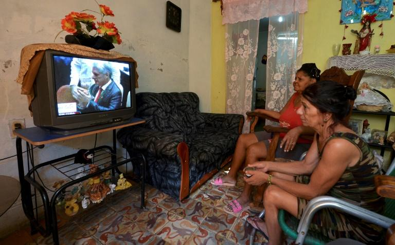 Cuban women watch on television in Havana as Cuba's new President Miguel Diaz-Canel (on screen) takes over from Raul Castro