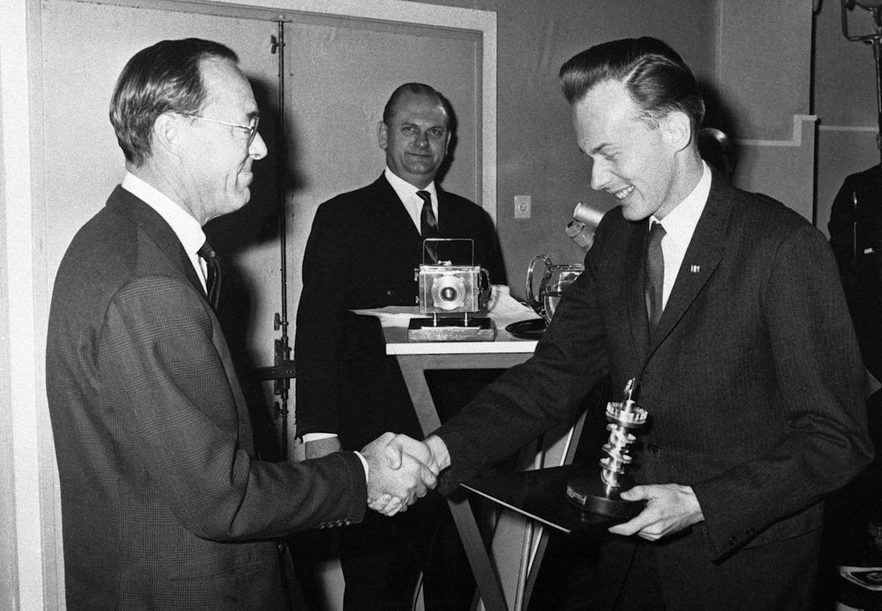 Prince Bernhard of the Netherlands, left, presents to Malcolm Browne, Associated Press correspondent photographer based in Saigon, Vietnam, the 'Golden Pier,' a symbolic prize, for his picture of a burning monk which was selected as overall winner and news category winner in the Seventh World Press Photo contest in The Hague, Netherlands on Dec. 14, 1963. Browne received his award at the opening of the exhibition of pictures entered for the important competitions. At center is Peter Van Breukelen, chairman if the World Press Photo Foundation. (AP Photo)