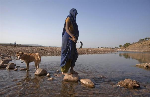 "Anguri (L), a 26-year-old pregnant woman in labour, steps on stones to cross a river while holding a sickle in her hand as she tries to reach a waiting maternity ambulance in a rural area near the remote village of Chharchh, in the central Indian state of Madhya Pradesh, February 24, 2012. In rural Madhya Pradesh, an innovative and free maternity ambulance service called ""Janani Express"", run in partnership between the state government and the United Nations Children's Fund (UNICEF), is trying to increase the number of babies born in clinics where proper care can be provided to the mothers and newborn children, and infant mortality can be decreased."