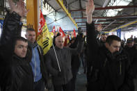Railway workers votes during a meeting of the CGT union in Rennes, western France, Monday, Dec. 9, 2019. Unions launched nationwide strikes and protests over the government's plan to overhaul the retirement system. Paris commuters inched to work Monday through exceptional traffic jams, as strikes to preserve retirement rights halted trains and subways for a fifth straight day. (AP Photo/David Vincent)