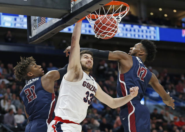 Gonzaga forward Killian Tillie (33) dunks between Fairleigh Dickinson's Elyjah Williams (21) and Kaleb Bishop (12) during the second half of a first-round game in the NCAA mens college basketball tournament Thursday, March 21, 2019, in Salt Lake City. (AP Photo/Rick Bowmer)