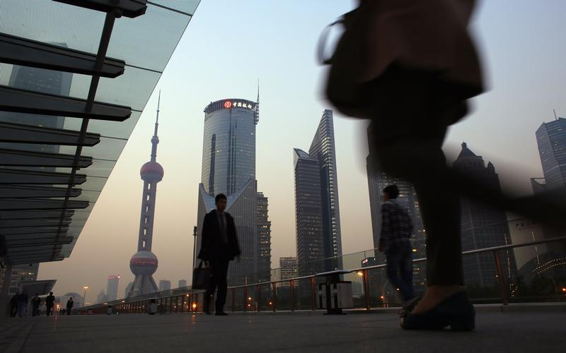 People walk along an elevated walkway at the Pudong financial district in Shanghai