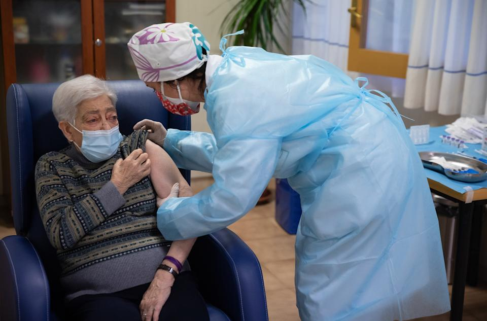 BARBASTRO, SPAIN - DECEMBER 27: In this handout photo, Lidia Navarro, 84, receives one of the first Pfizer/BioNTech Covid-19 vaccines in Spain at the Somontano nursing home on December 27, 2020 in Barbastro, Spain. Spain will begin to administer the coronavirus vaccine developed by Pfizer and BioNTech on December 27. With 1.84 million cases recorded since the start of the pandemic, Spain has reported almost 50,000 covid-19 deaths. (Photo by Alvaro Calvo/Government of Aragon via Getty Images)