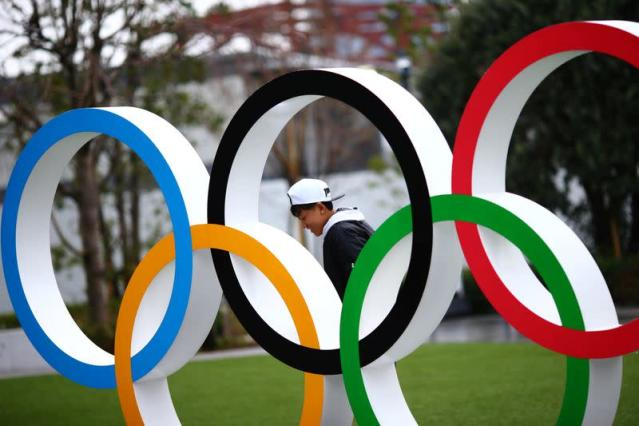 A man is pictured through The Olympic rings in front of the Japan Olympics Museum in Tokyo