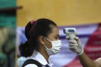 A school girl, left, has her temperature checked before she enters the Santhormok high school in Phnom Penh, Cambodia, Monday, Nov. 2, 2020. Schools throughout Cambodia that had been shut in March because of the coronavirus crisis reopened Monday, but with limits on class sizes and hours. (AP Photo/Heng Sinith)
