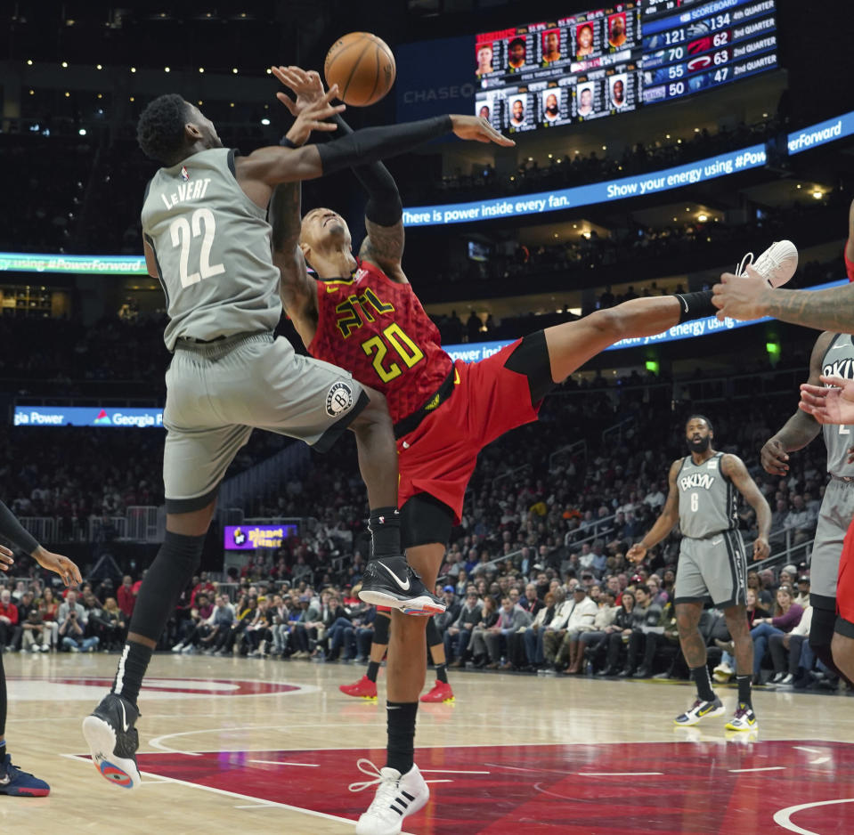 Brooklyn Nets Caris LeVert (22) battles for the ball with Atlanta Hawks John Collins (20) in the second half of an NBA basketball game Friday, Feb. 28, 2020, in Atlanta. (AP Photo/Tami Chappell)