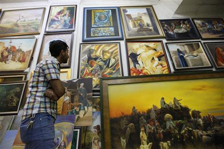 A customer looks at paintings at a gallery in Baghdad's Karrada district, September 18, 2013. REUTERS/ Thaier Al-Sudani