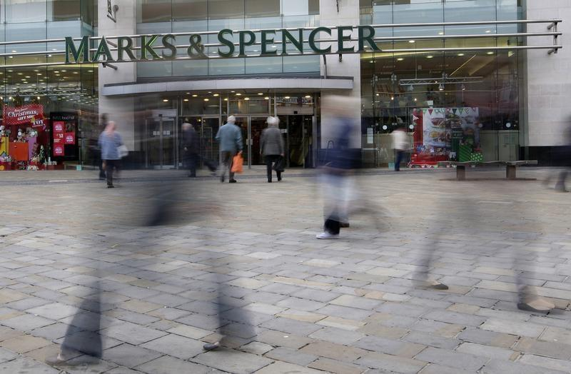 People walk past a Marks and Spencer store in Leicester