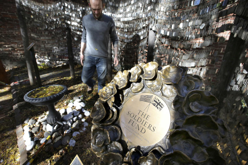 In this Wednesday, Nov. 7, 2018 photo Tim Wenrich, of Boston, caretaker at Old North Church, stands near a bronze wreath, right, that is part of a memorial that honors fallen soldiers from the U.S. and Britain, on the grounds of the church in Boston. Since 2005, thousands of military dog tags have hung like wind chimes outside the church in touching tribute to American forces killed in Iraq and Afghanistan. The new plaque and wreath will explain the meaning of the dog tags and acknowledge Britain's contribution and sacrifice. (AP Photo/Steven Senne)