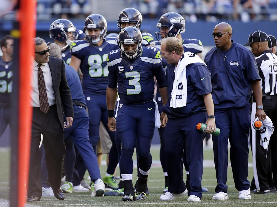 Seattle Seahawks QB Russell Wilson, middle, is going through a lot to play Sunday (AP).