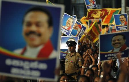 A police officer stands guard among images of Sri Lankan President Mahinda Rajapaksa during Rajapaksa's final rally ahead of presidential election in Piliyandala