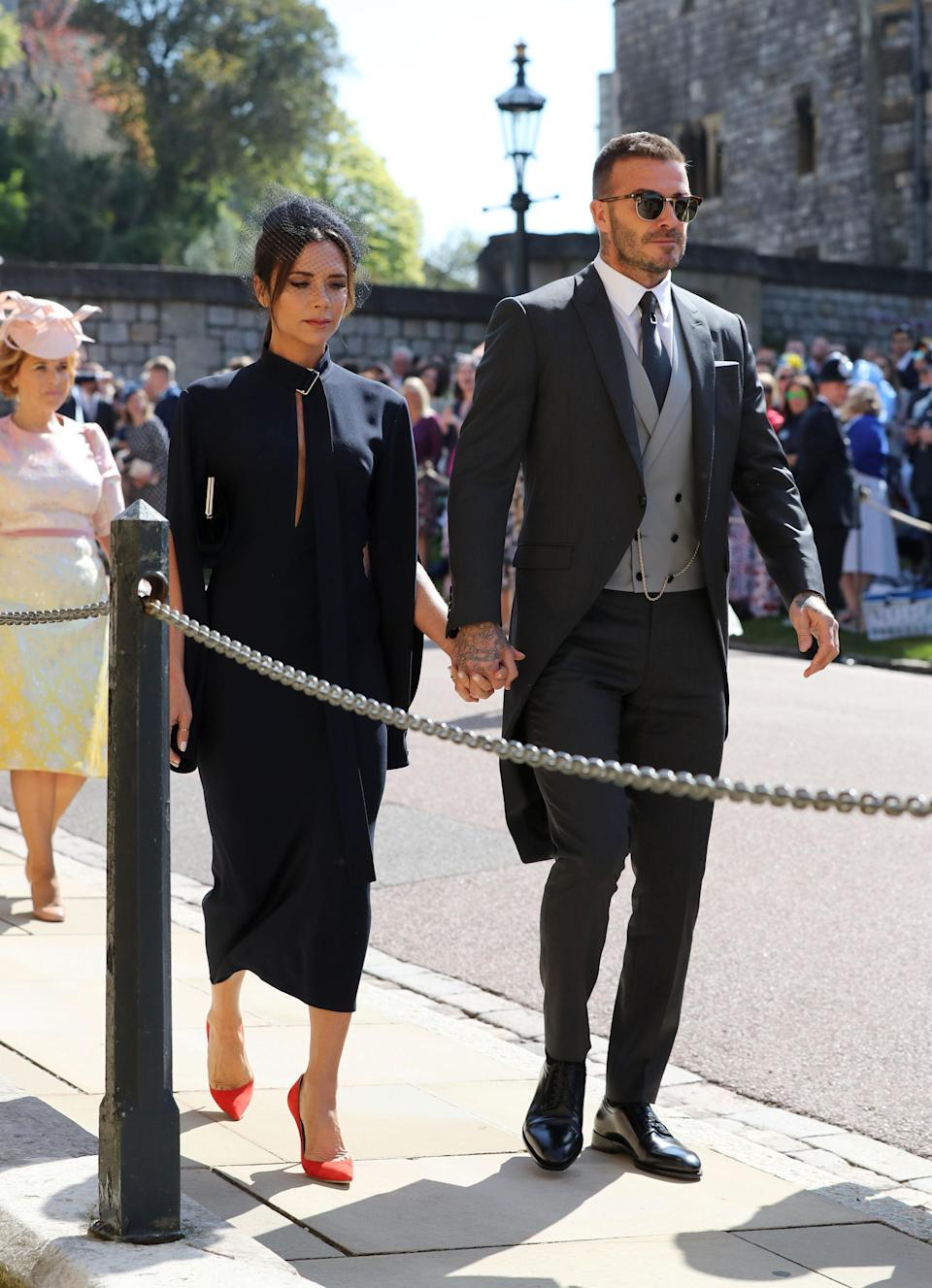 <p>Wearing her own label and Manolo Blahnik, Victoria arrives with husband David, wearing a suit by Dior Homme. <em>[Photo: PA]</em> </p>