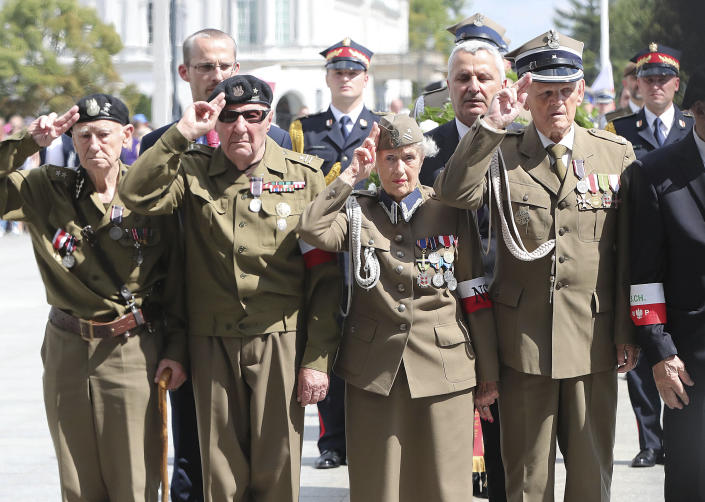 Polish officials and war veterans pay tribute to a World War II-era underground force that collaborated with Nazi German forces toward the end of the war in their battle against the Communists, who were imposing control on the nation, in Warsaw, Poland, Sunday, Aug. 11, 2019. President Andrzej Duda's official patronage and the presence of ruling party officials underlined the right-wing government's rehabilitation of a partisan unit that fought both Germans and Soviets and which is celebrated by the far right .(AP Photo/Czarek Sokolowski)