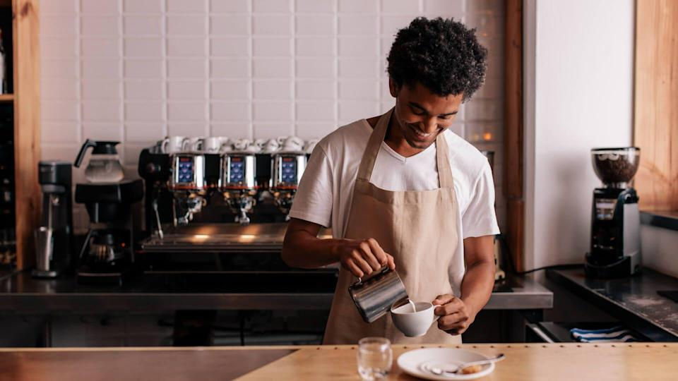 young-african-pouring-milk-in-the-cafe