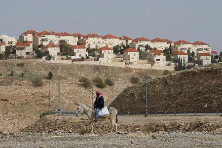 FILE PHOTO: A Palestinian man rides a donkey near the Israeli settlement of Maale Edumim, in the occupied West Bank, December 28, 2016. REUTERS/Baz Ratner/File photo