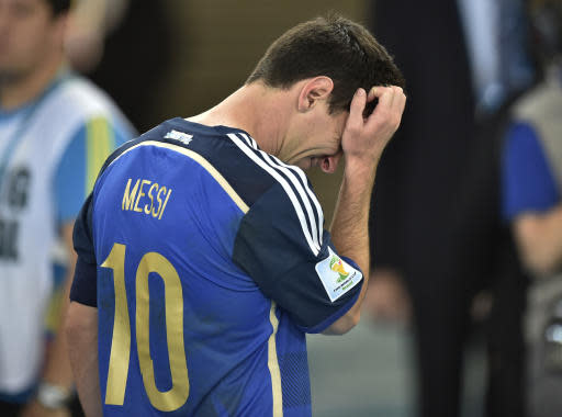 FILE - In this July 13, 2014, file photo, Argentina's Lionel Messi scratches his head as he goes up to get his runners-up medal after the World Cup final soccer match between Germany and Argentina at the Maracana Stadium in Rio de Janeiro, Brazil. Cristiano Ronaldo and Lionel Messi put up impressive numbers, in life and on the field, going into a fourth World Cup for each. So much has happened for football's standout stars since the 2014 tournament left both still lacking the game's most coveted prize. (AP Photo/Martin Meissner, File)