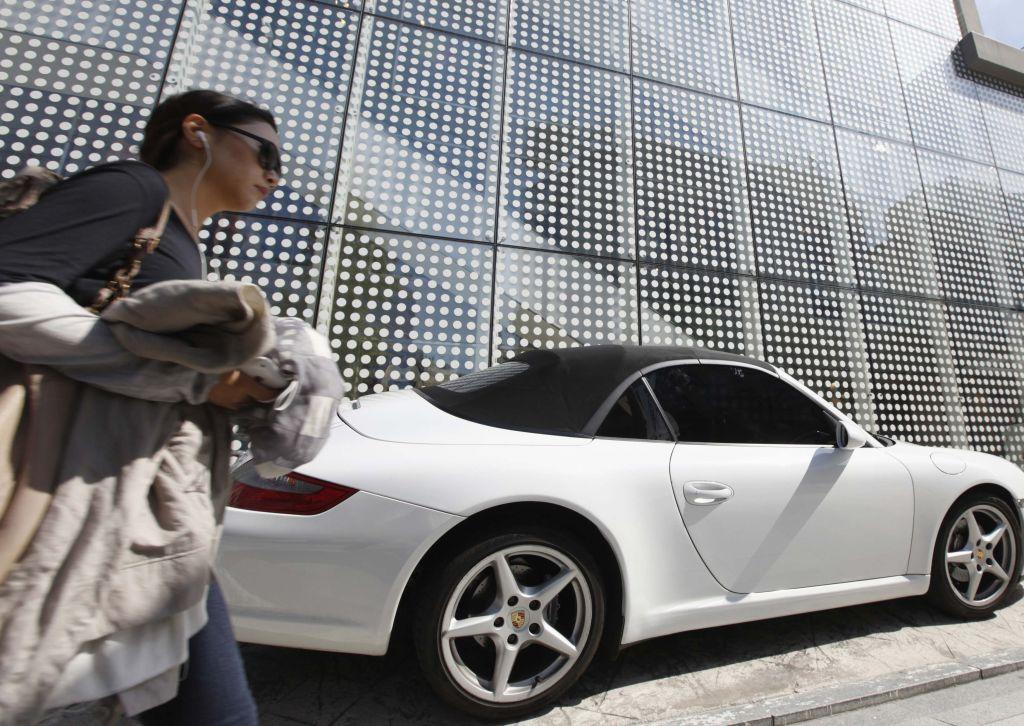 "A woman walks past a Porsche on the Garosugil or the Tree-Lined Street in the Gangnam area of Seoul. Gangnam is the most upmarket neighbourhood in the South Korean capital. Known as Seoul's ""Beverly Hills"", its streets are lined with designer-brand shops and trendy bars and restaurants. Chubby South Korean singer Psy was raised in the area and his hit song ""Gangnam Style"", with his quirky horse-riding dance, has stormed to number one in charts around the world while the video has been watched more than 454 million times on YouTube since July."