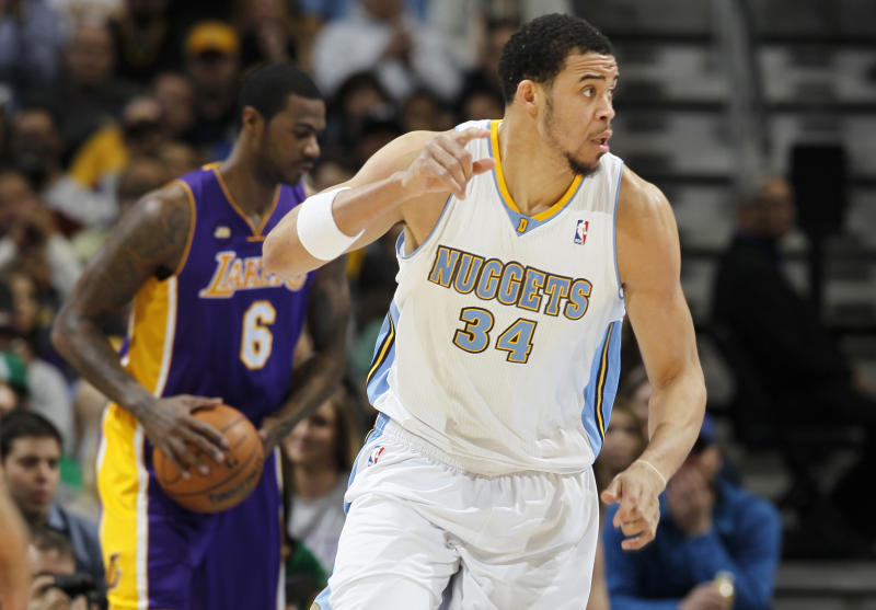 Denver Nuggets center JaVale McGee, front, celebrates scoring on a dunk as Los Angeles Lakers forward Earl Clark reacts in the background in the first quarter of an NBA basketball game in Denver on Monday, Feb. 25, 2013. (AP Photo/David Zalubowski)